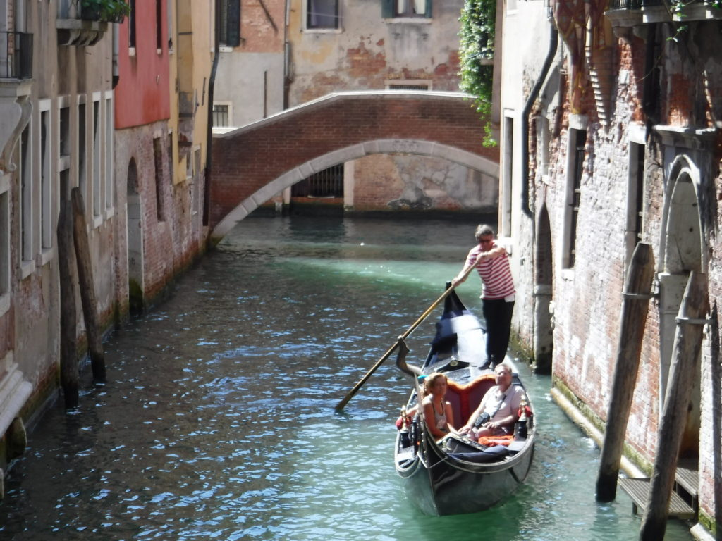 Gondolieri with tourists in a smaller canal